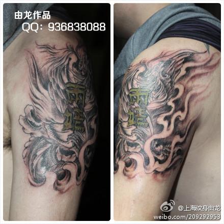 > 上海纹身由龙刺青作品手臂纹身      手臂黑灰凤凰加文字的纹身,这图片